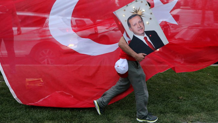 An Erdoğan supporter carries a poster with his face in front of a Turkish flag.