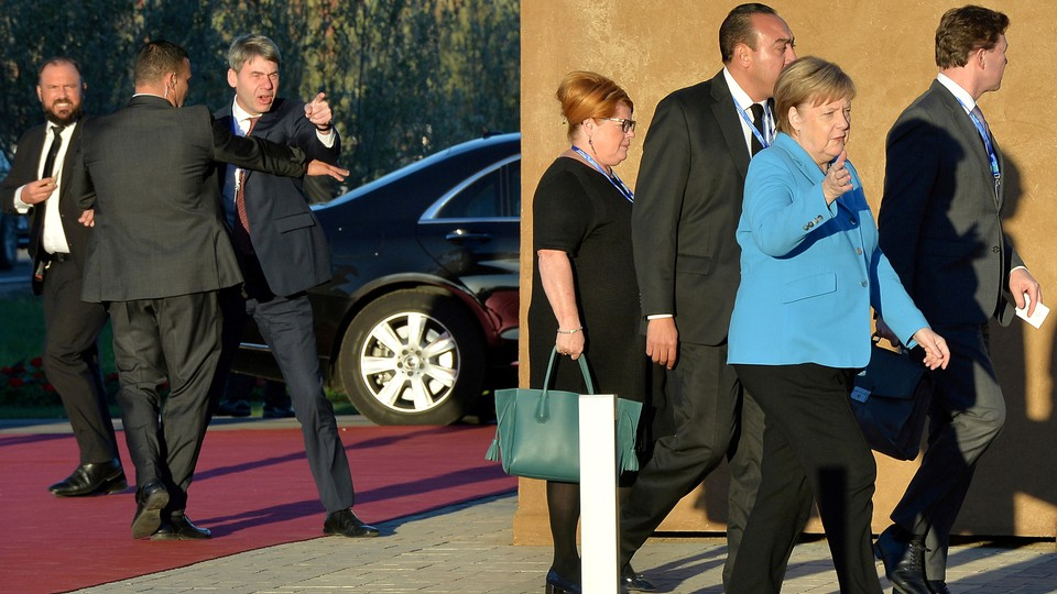German Chancellor Angela Merkel arrives in Marrakech for the signing of a United Nations migration compact as man gestures angrily in the background.