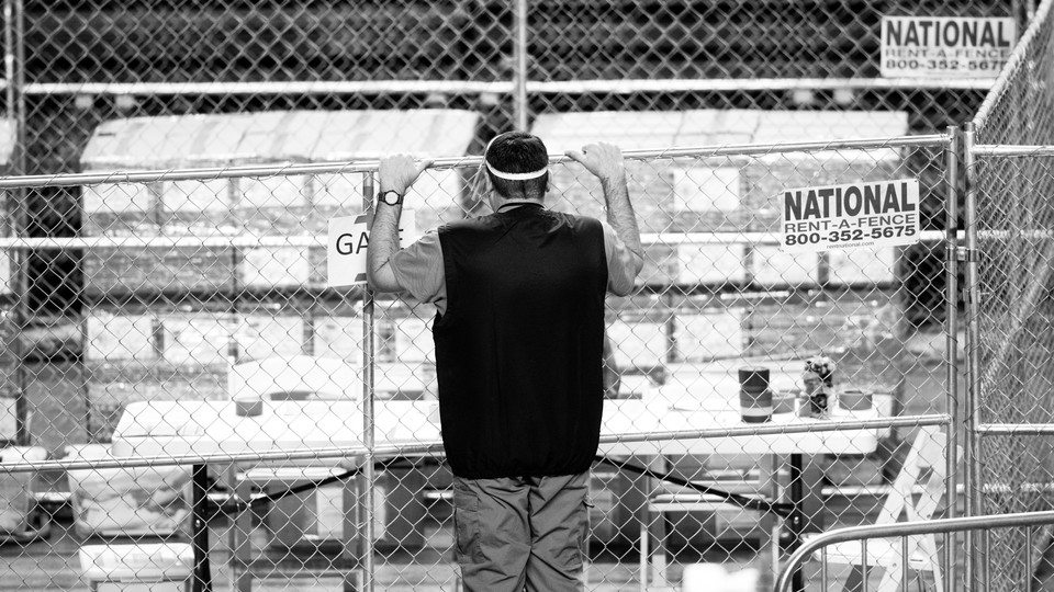 A contractor working for Cyber Ninjas, who was hired by the Arizona state Senate, looks at ballots from the 2020 general election behind a fence.