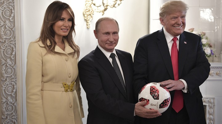 Melania Trump, Vladimir Putin, and Donald Trump pose with a soccer ball.