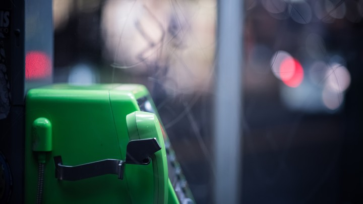 A green telephone in a phone booth