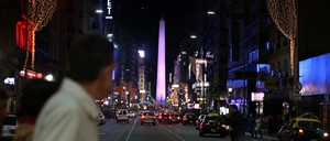 People cross Corrientes Avenue in Buenos Aires at night, with the Obelisk in the background.