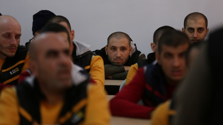 Former ISIS members sit at desks in a classroom.