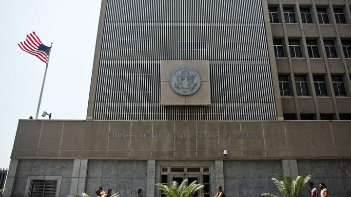 Pedestrians walk past the U.S. embassy in Tel Aviv.