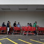 Rain-doused people with shopping carts wait in line on a covered parking lot in front of a grocery store