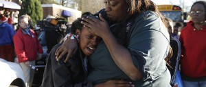 A woman comforts a distraught child after a school shooting in Atlanta.