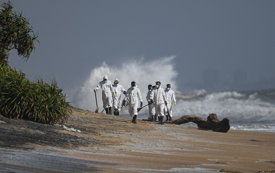 About a half-dozen Navy members dressed in protective gear walk on a polluted beach.