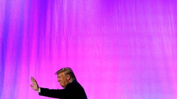 President Donald Trump waves in front of a pink background.