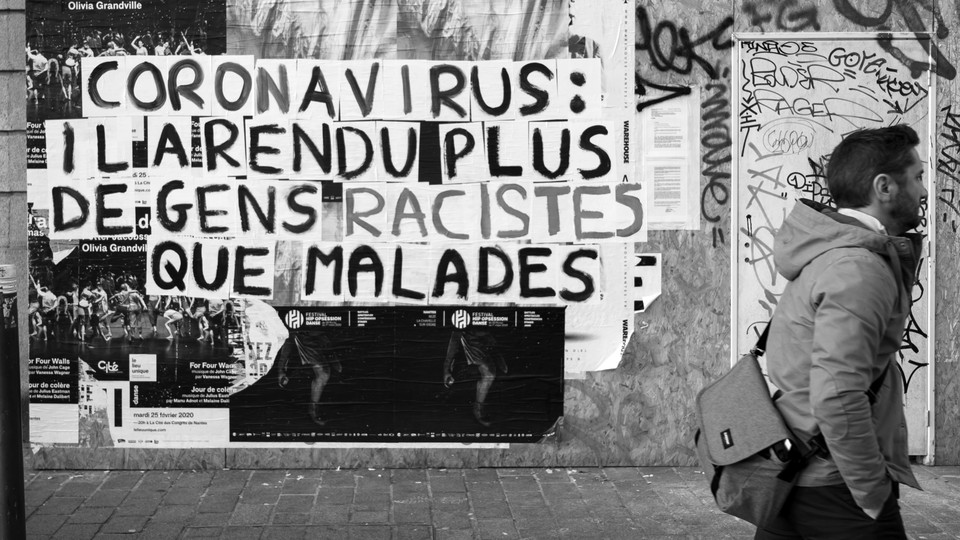 A sign in black and white denounces coronavirus-related racism in France.