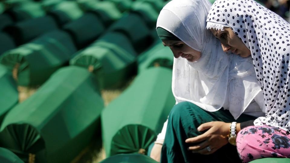 Muslim women mourn on July 11, 2016, near coffins of newly identified victims of the 1995 Srebrenica massacre.