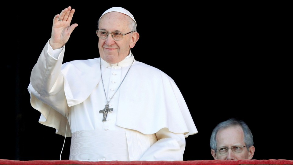 Pope Francis waves from the balcony of Saint Peter's Basilica at the Vatican on Christmas in 2018.