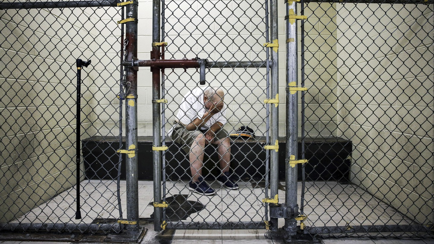A man in a jail cell with his head in his hands