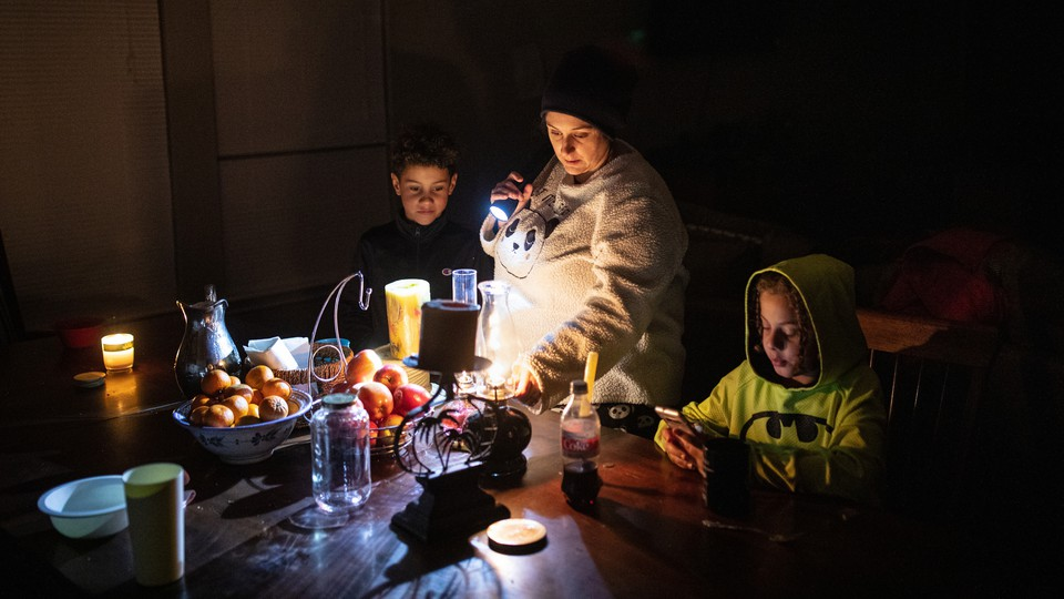 A woman adjusts an oil lamp in the dark while standing between her two sons