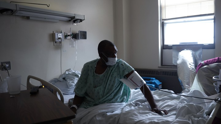 A masked man in a green gown sits up in a hospital bed, wearing medical cuff around his upper arm