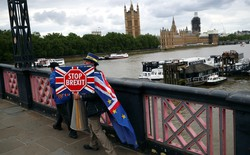 "An anti-Brexit campaigner crosses a bridge opposite Parliament in London holding a ""Stop Brexit"" sign."