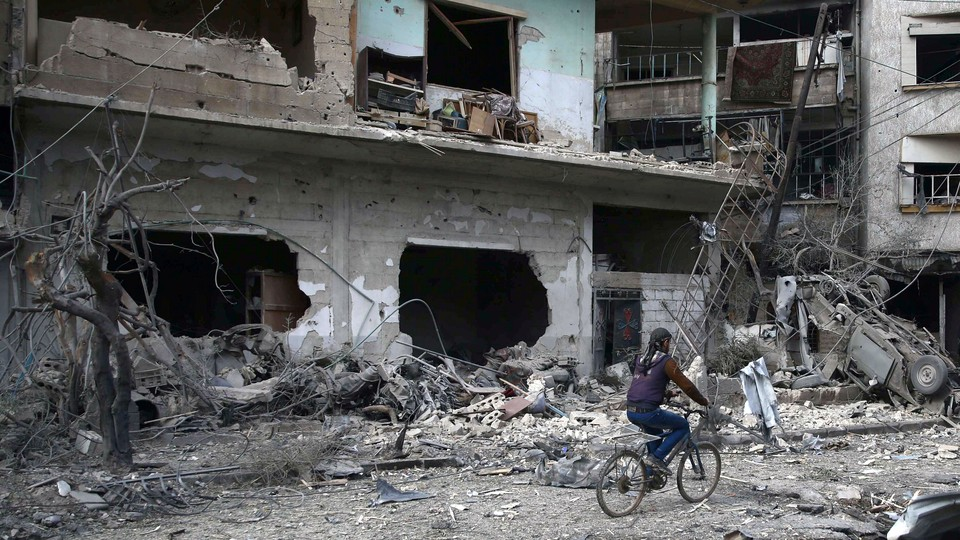 A boy rides his bicycle past the rubble of bombed-out buildings.