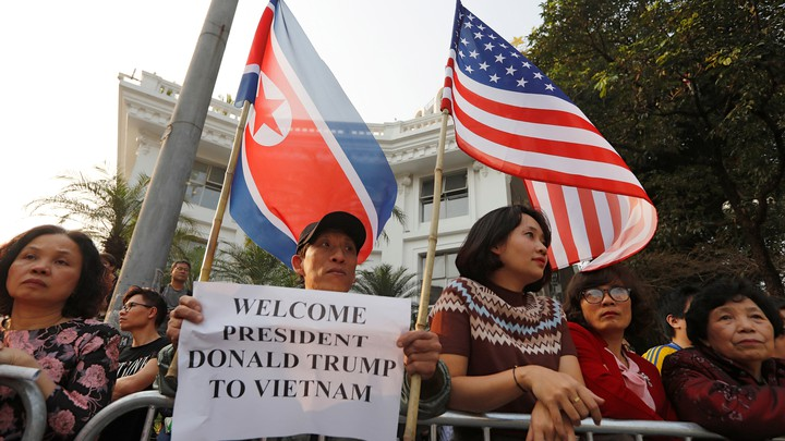 People hold North Korean and American flags near Hanoi's Metropole hotel, where Donald Trump and Kim Jong Un were meeting.