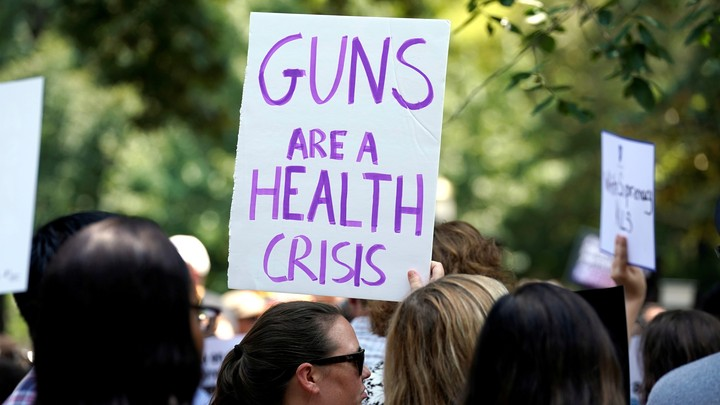 "Protester holding a sign that says ""Guns are a health crisis"""