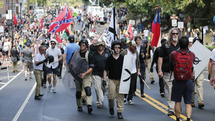 White supremacists marching in Charlottesville, Virginia, on August 12, 2017, one waving a Confederate flag