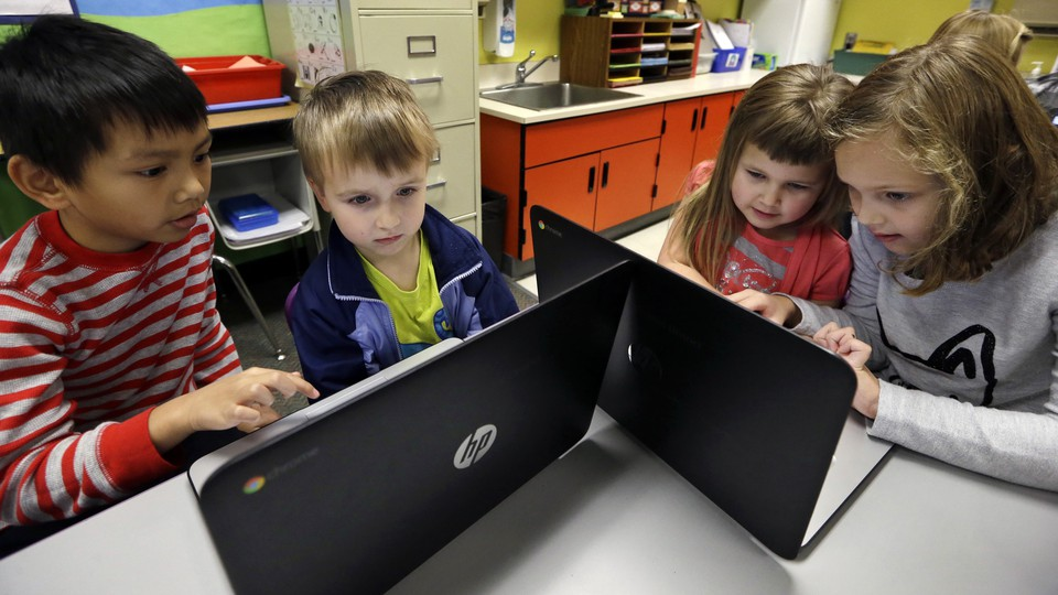 Two boys and two girls huddle around two laptops.