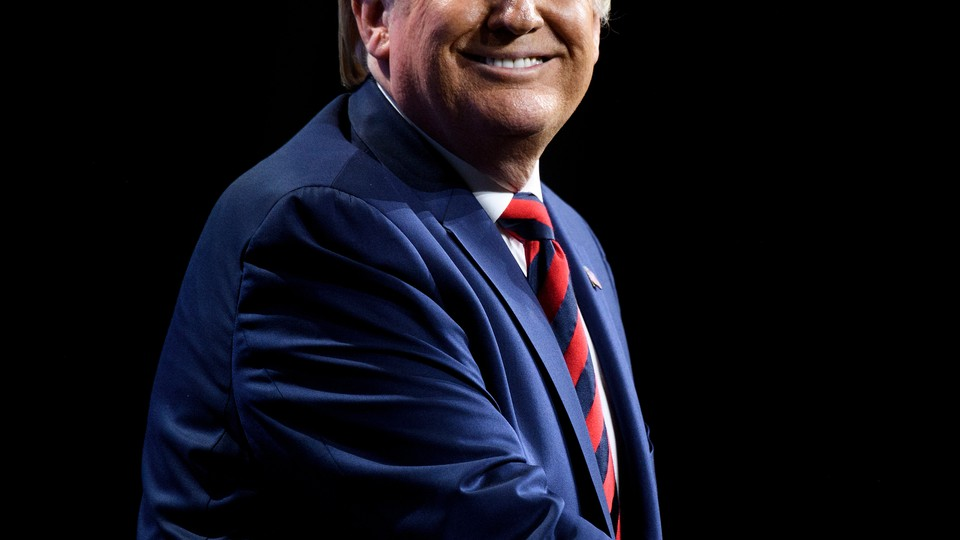 President Donald Trump looking to his right and smiling, wearing a navy suit with a red-and-blue-striped tie