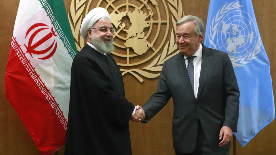 Iran's President Hassan Rouhani shakes hands with United Nations Secretary General António Guterres in front of their respective flags.