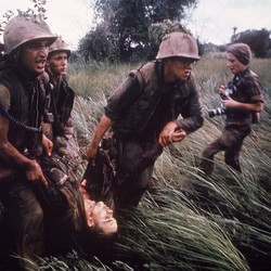 Marines recovering a dead comrade while under fire in South Vietnam. Photographer Catherine LeRoy holds cameras behind them.