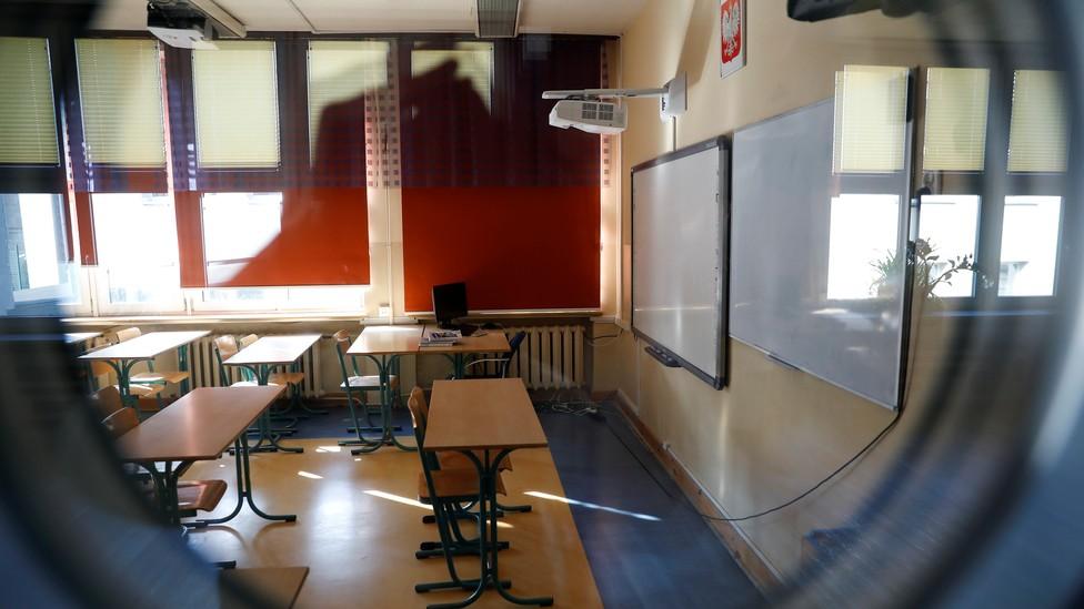 Empty classroom seen through a peephole.