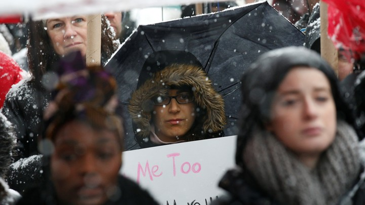 "A woman holds a ""Me Too"" sign."
