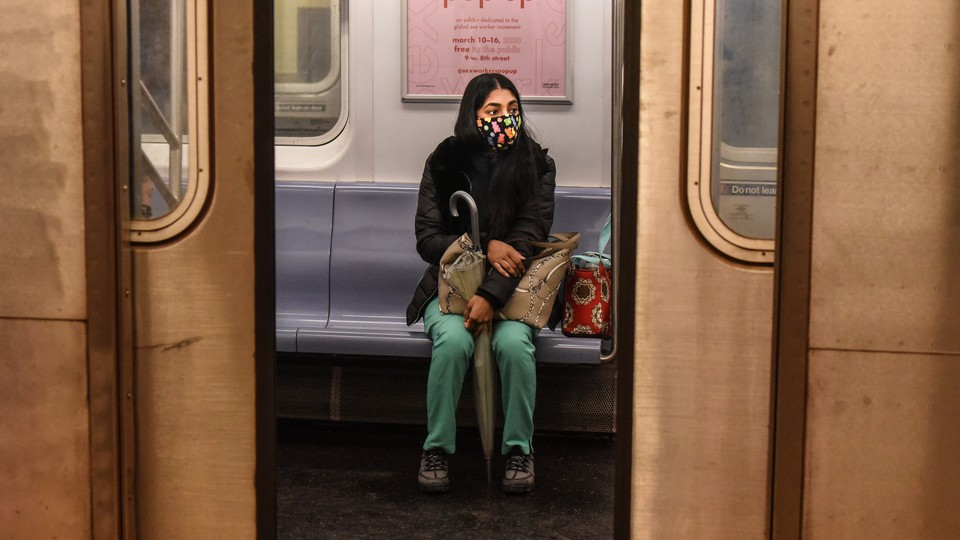 A woman sitting in a subway car with a face ams