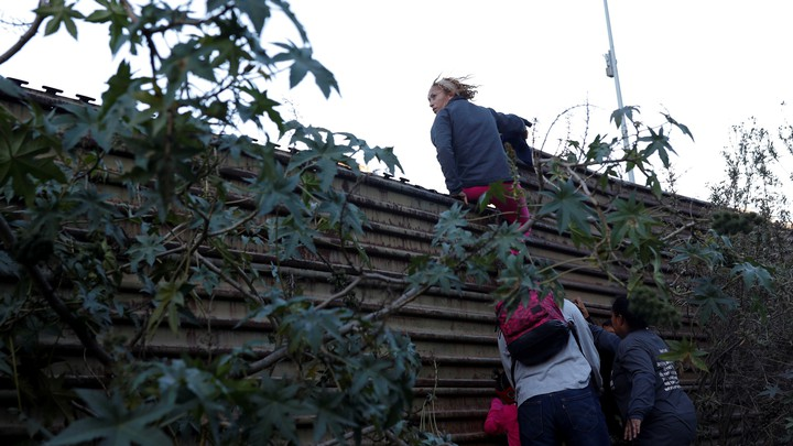 Migrants try to jump over the border wall to cross from Mexico to the U.S. on December 15, 2018.