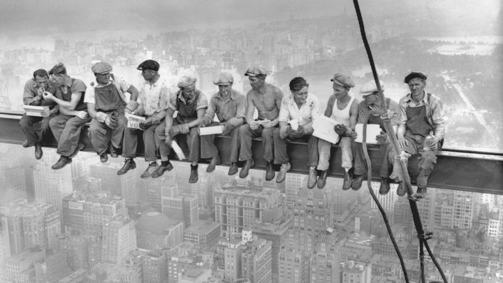 A group of steel workers eats lunch on a beam hundreds of feet above New York City.