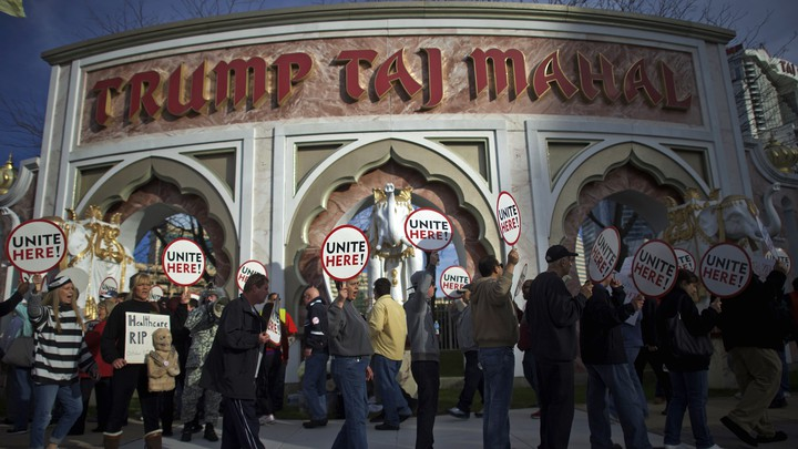 """People picket with signs that say """"Unite here"""" in front of the Trump Taj Mahal casino."""