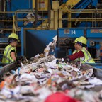 Workers in a recycling facility sort material on a conveyer belt.