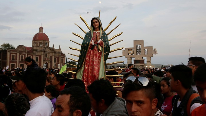 Pilgrims carry a statue of the Virgin of Guadalupe as they arrive at the Basilica of Guadalupe.