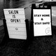 """A photo of two road-side signs. One says, """"Salon is open!"""" The other says, """"Stay home and stay safe!"""""""