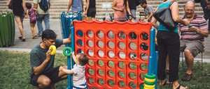 A toddler and a man play a giant Connect Four game in a park.