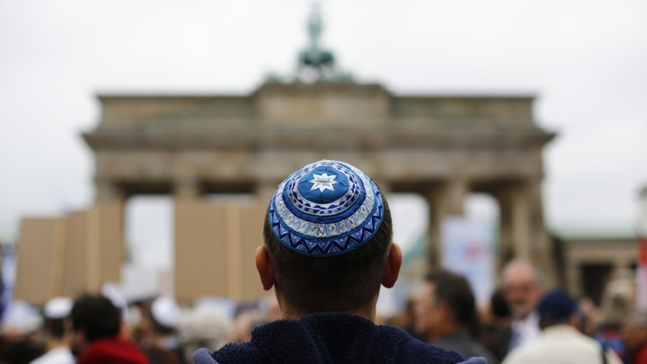 A man waits for the start of a demonstration against anti-Semitism in Berlin.