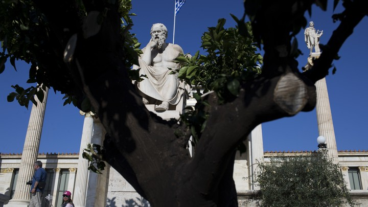 A statue of Socrates is visible behind a tree.