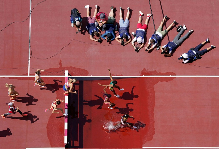 A gathering at the water hole: About 10 photographers lie prone near a water jump as runners pass by and splash.