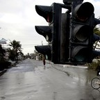 A traffic light dangles from its wire on Simonton Street in downtown Key West, Florida, after Hurricane Wilma