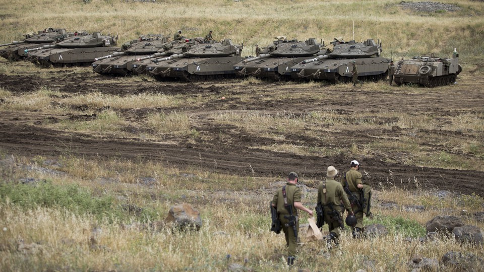 Three soldiers walking in front of a line of tanks