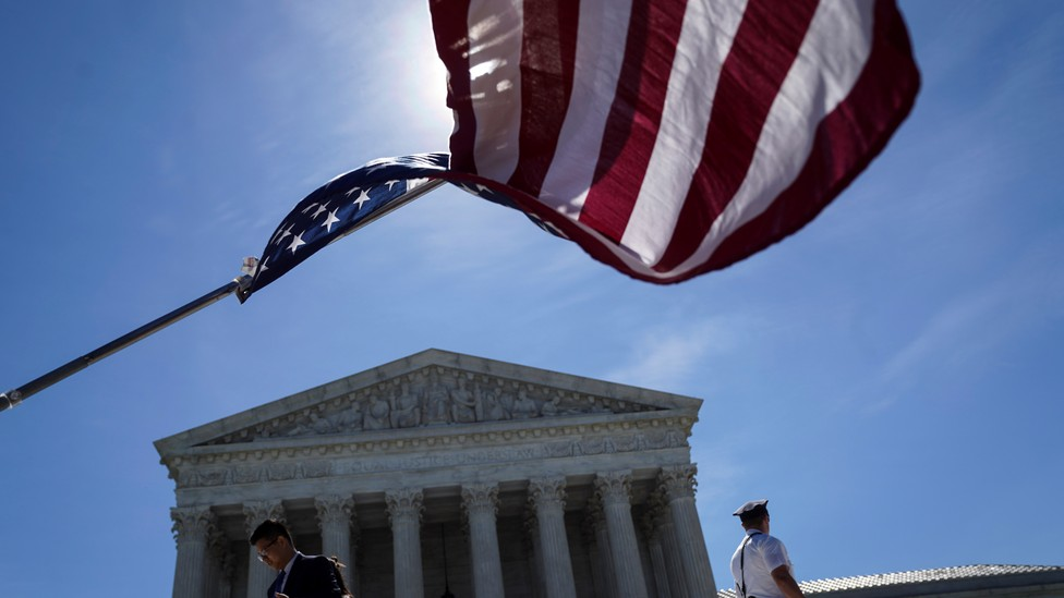 An American flag waving in front of the Supreme Court