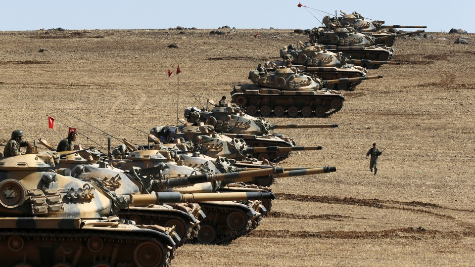 Turkish army tanks take up position on the Turkish-Syrian border near the southeastern town of Suruc in Sanliurfa province October 6, 2014