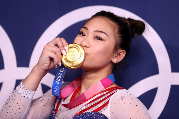 A gymnast kisses her gold medal while posing.