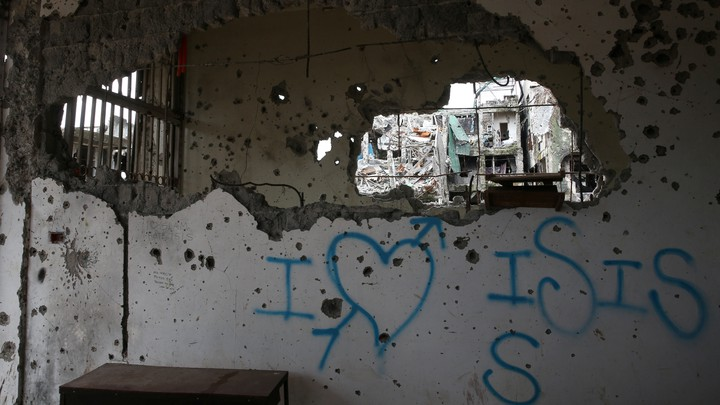 """Graffiti that reads """"I love ISIS"""" is seen in a damaged building in Marawi City, Philippines."""
