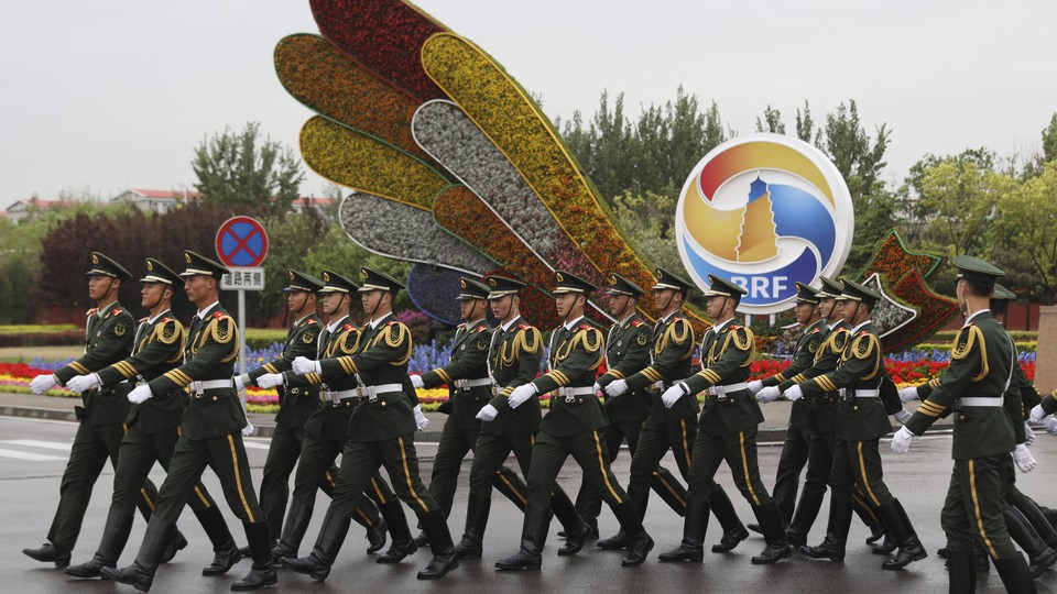 Chinese paramilitary policemen walk past a display ahead of Beijing's Belt and Road Forum.