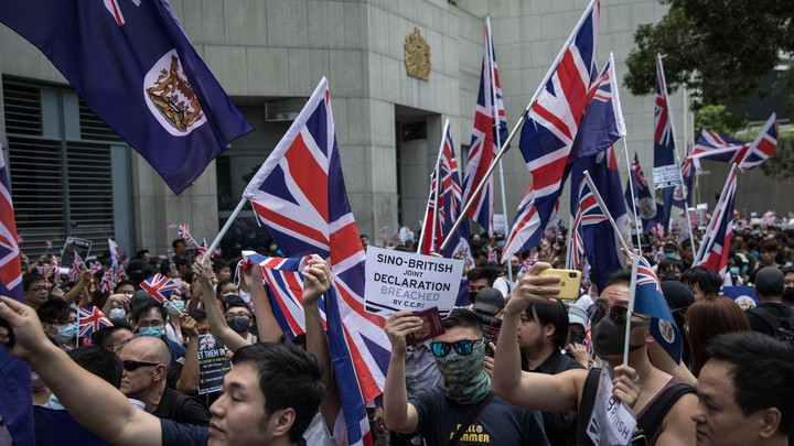 Pro-democracy protesters wave flags outside of the UK Embassy in Hong Kong in September 2019.