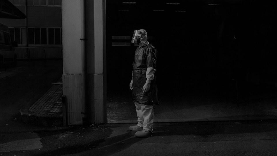 A person in a protective suit stands in the dark.
