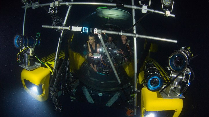 People in a submersible with lots of lights and cameras